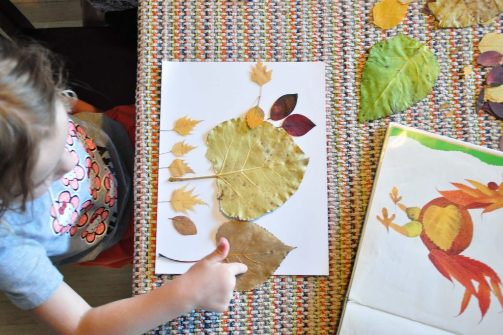 A preschooler designing a picture with leaves