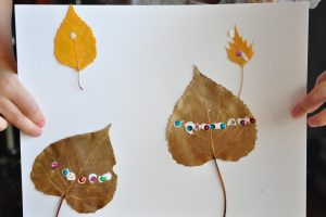 a preschooler's hands holding up her leaf art scene