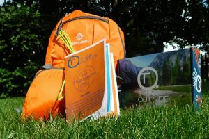 An orange backpack, guide book, and think outside subscription box all piled on the ground