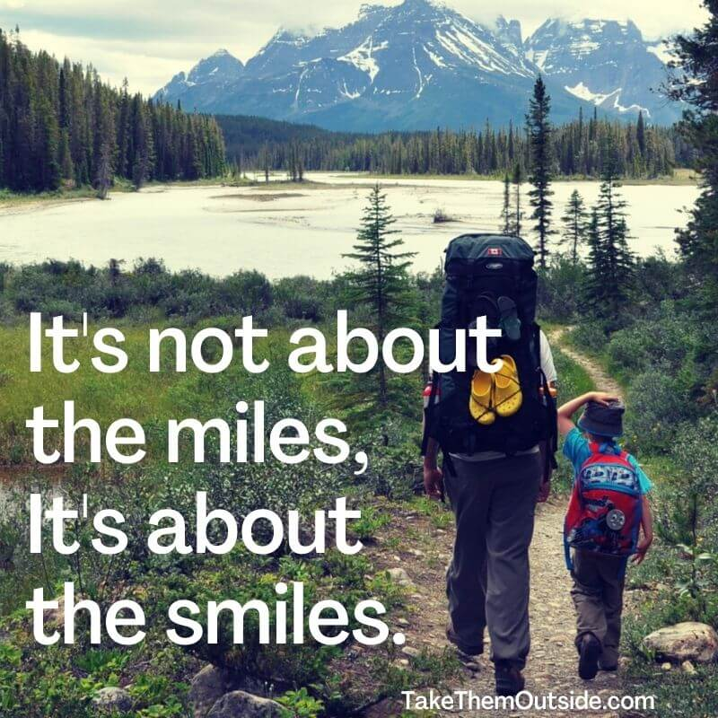 """dad and boy hiking in the mountains, text reads """"it's not about the miles, it's about the smiles"""""""