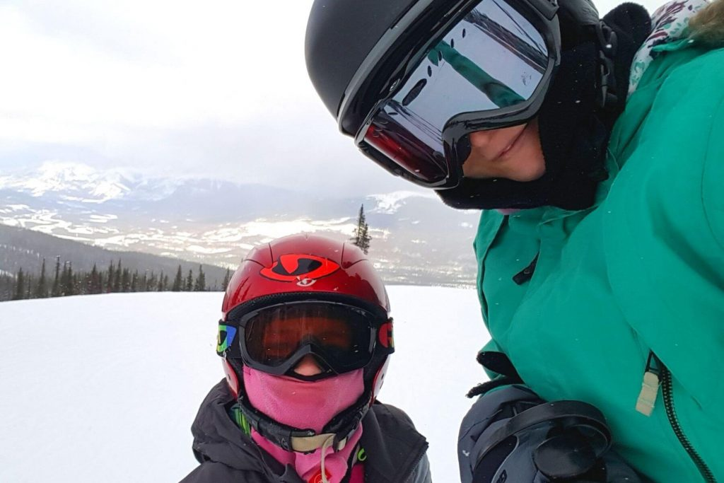 A mom and girl wearing ski helmets and goggles to stay warm in the winter