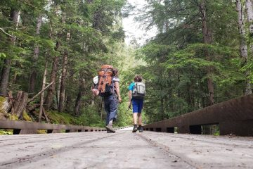 a mom and boy wearing backpacks hiking in the woods