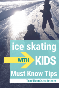one kid pulling another on a sled while they skate on a frozen lake at sunset