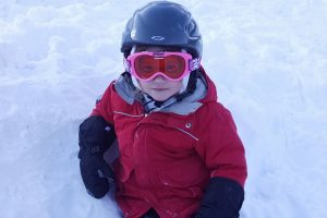young kid wearing a helmet and ski goggles