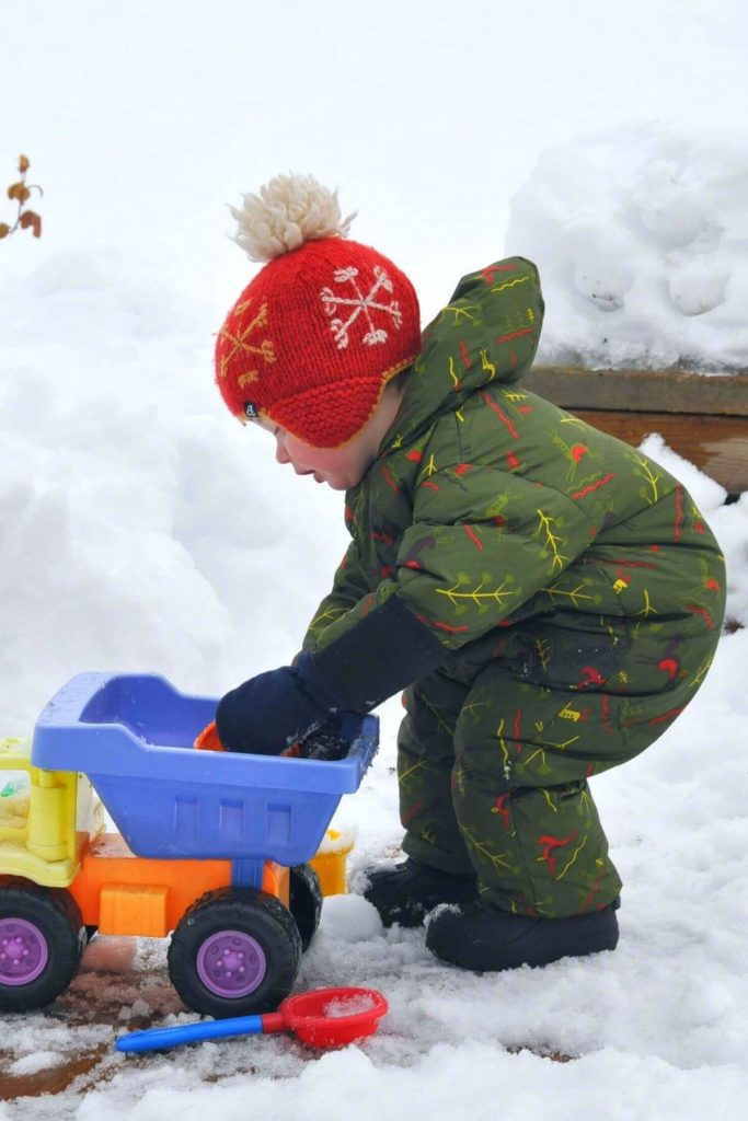 a toddler wearing a one-piece snowsuit to stay warm in the snow