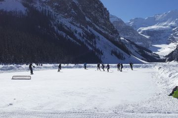 people playing pond hockey on the frozen lake louise in banff national park