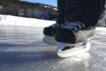 a close up of kid's hockey skates on a frozen lake