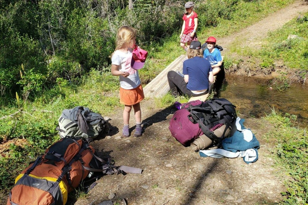 kids on a hike taking a break on the trail by a creek