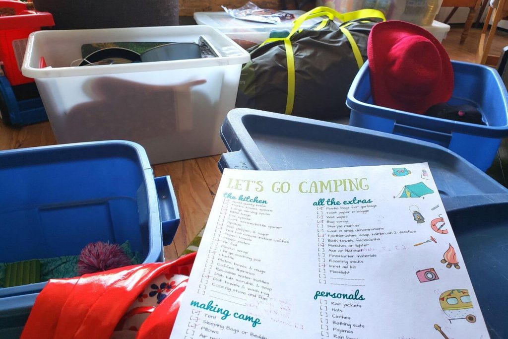 a printed camping checklist being used to pack for a camping trip