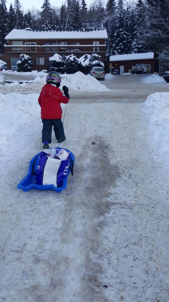a small child pulling a red snow sled carrying ice skates