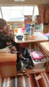 Kids eating breakfast at a table inside a vintage rv trailer