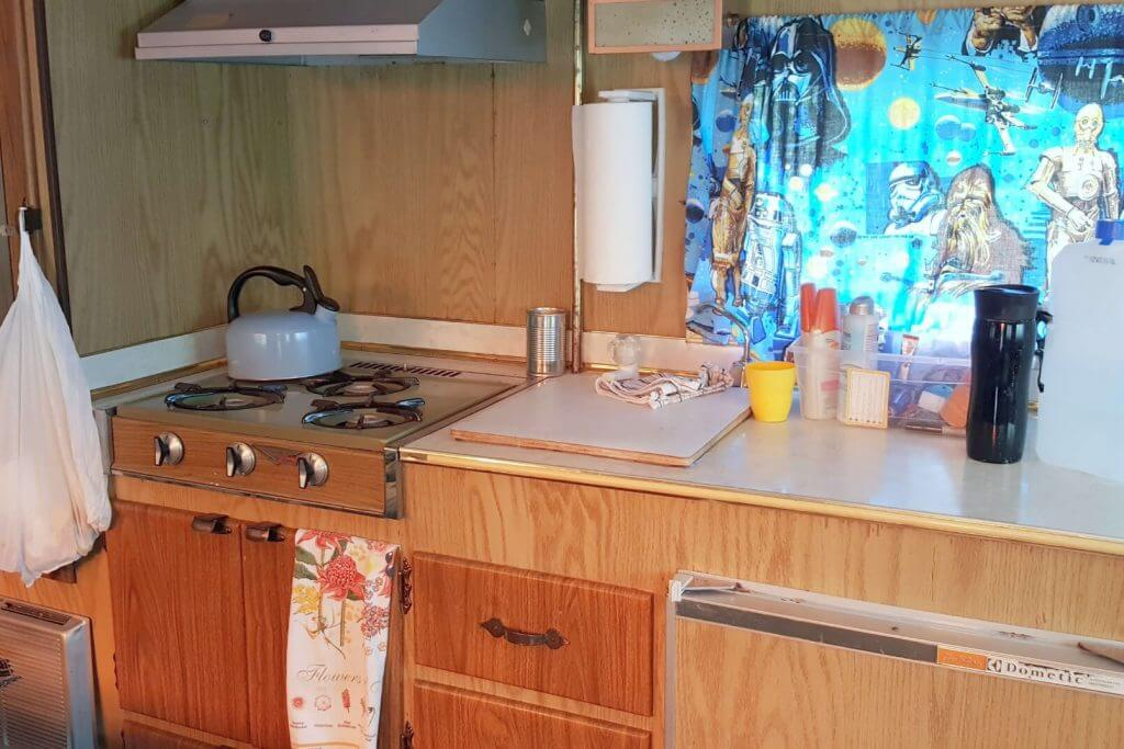 The counter and stove top inside a vintage rv camper triailer