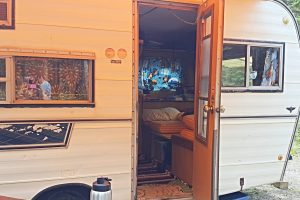 A beige vintage trailer with the door wide open to see inside