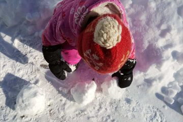 a toddler wearing a pink snowsuit making snowballs in the snow