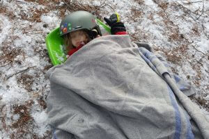 a toddler wearing a ski helmet asleep outdoors in the winter