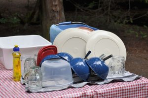 Camping dishes washed and drying on a red checkered picnic table