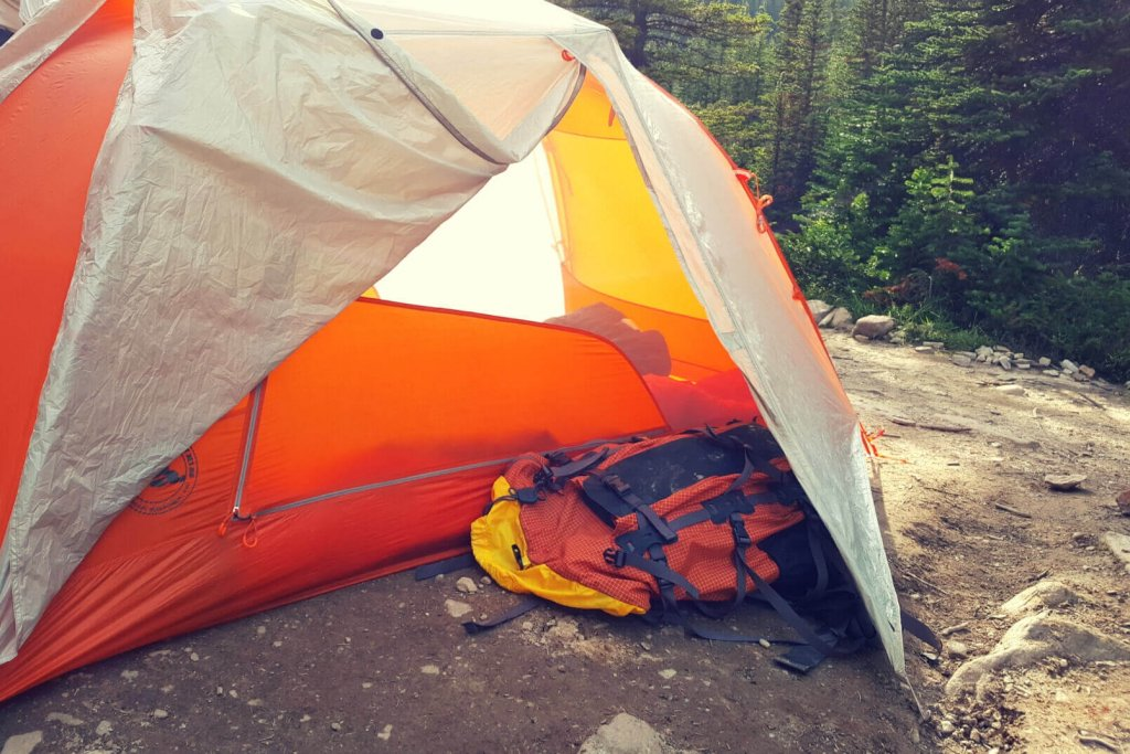 An orange tent and backpack