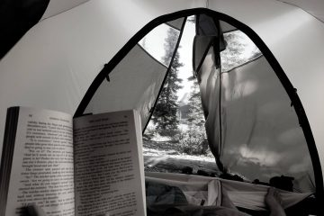 someone reading a book while lying in a camping tent