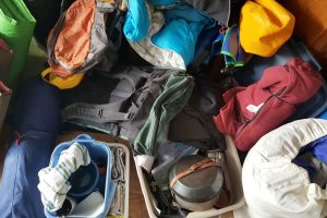 A pile of camping gear - sleeping bags, cooking gear, sleep pads, and more