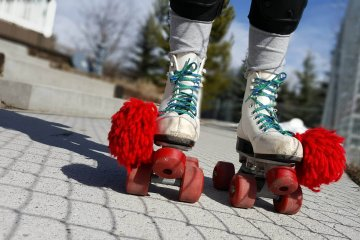 white roller skates with a red pompom
