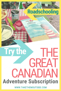 A booklet from the Great Canadian Adventure Subscription being used by a family eating dinner at a picnic table
