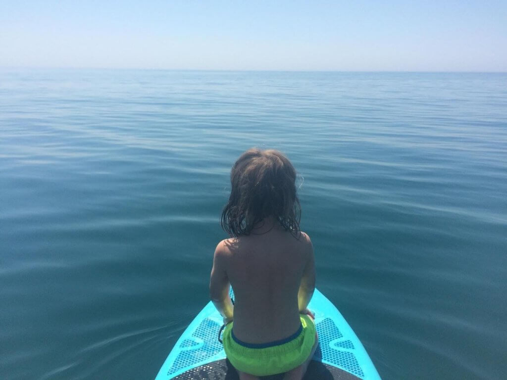 A toddler sitting on the front of a blue paddle board in the open water