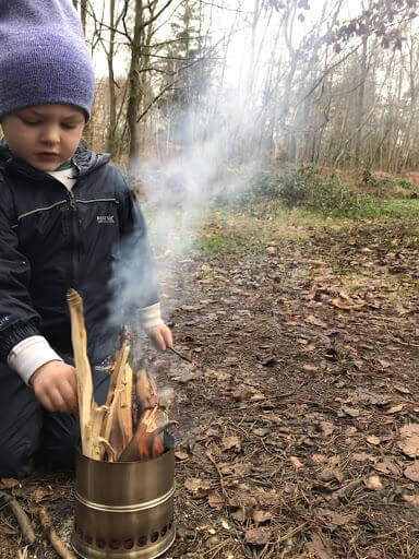 A preschooler learning how to start a small safe fire.
