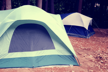 Two dome tents set up in a wooded area