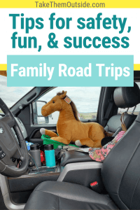 a giant stuffed horse sitting in the passenger seat of a truck during a family road trip