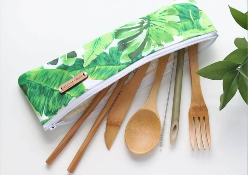 A bamboo reusable cutlery set with leaf patterned zippered pouch