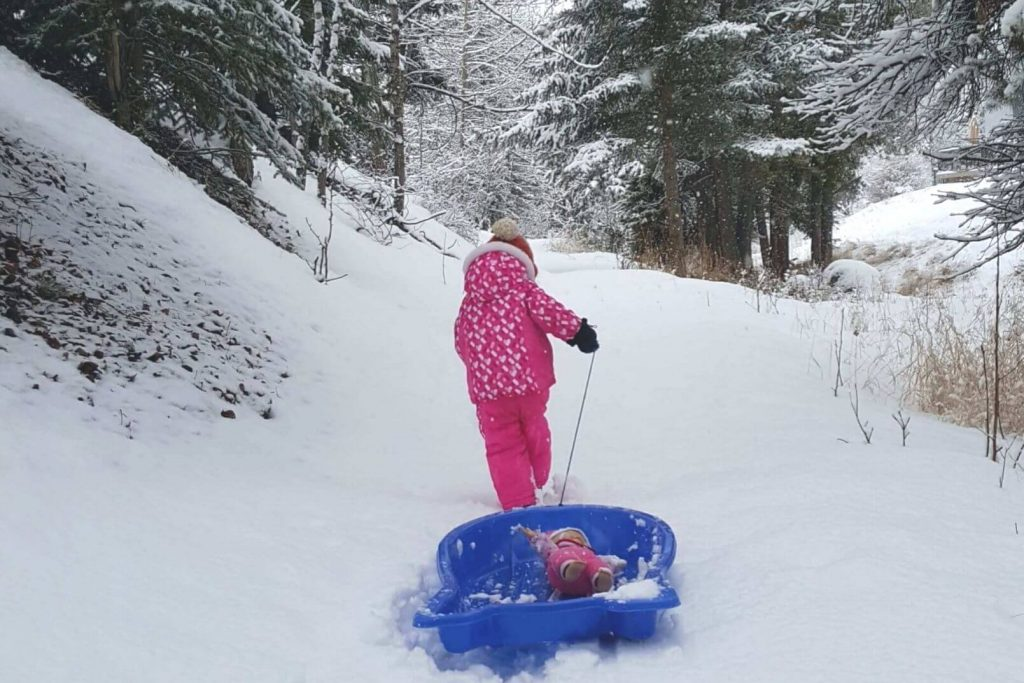 a little kid pulling her doll in a sled through the winter snow