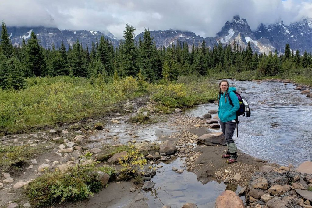 A woman walking a very wet and muddy trail in the Tonquin Valley