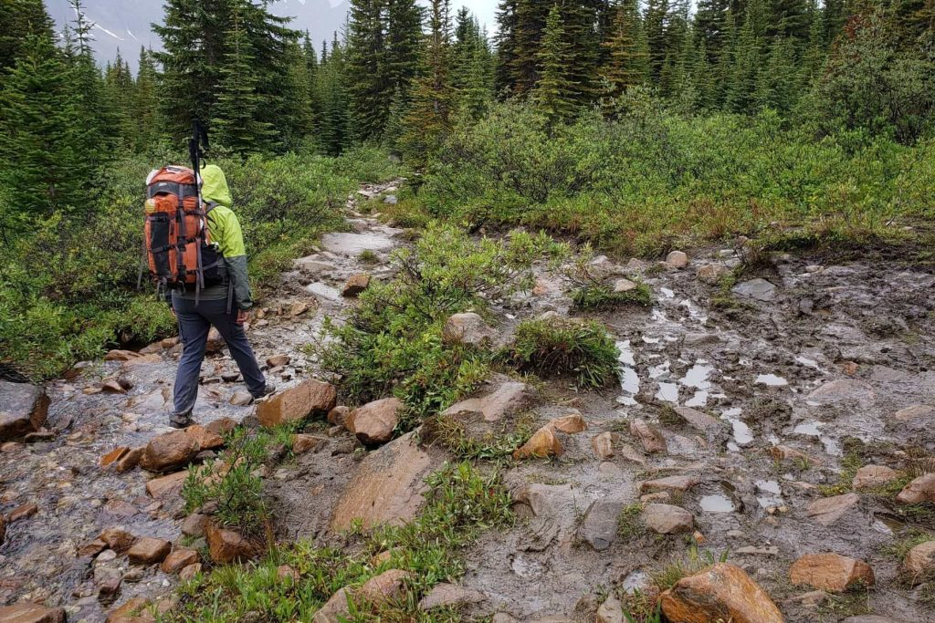 A man with a large backpack hiking on a wet and rocky forested trail