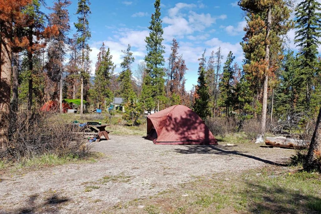 An orange tent set up at a campsite in Wabasso Campground, Jasper National Park