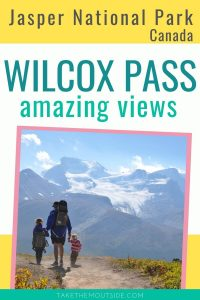 a dad hiking with 2 young kids with a glacier in the distance in jasper national park