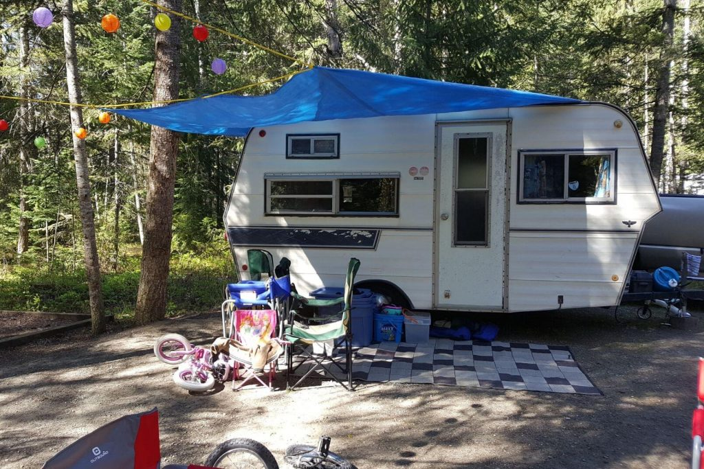A family set up at the campground with a vintage trailer, some bikes, and toys