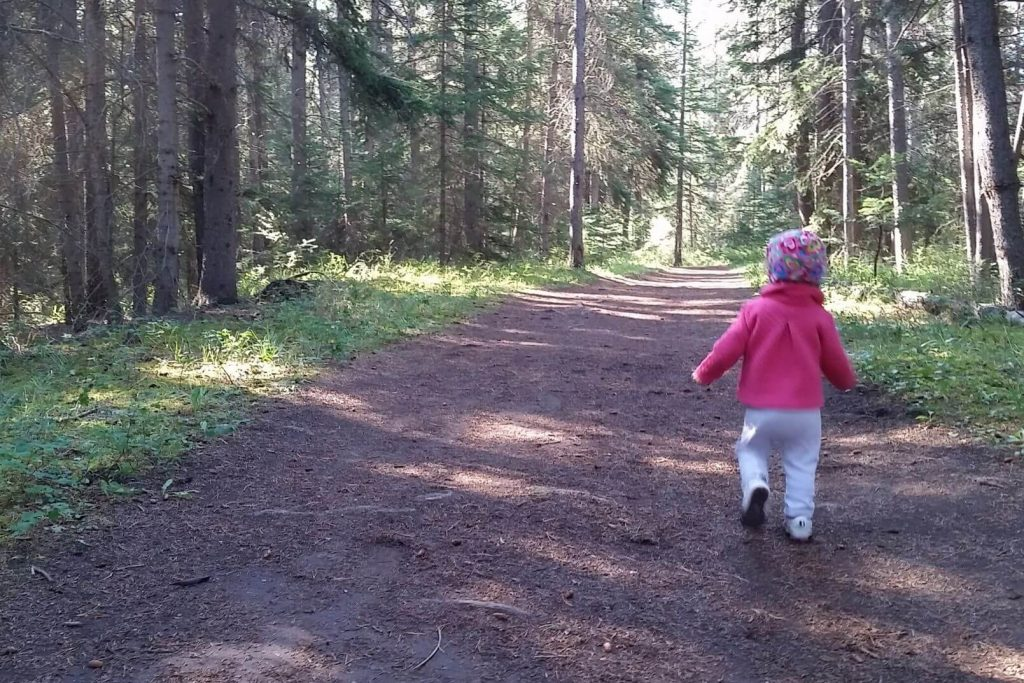 a toddler running ahead on a hiking trail through the woods