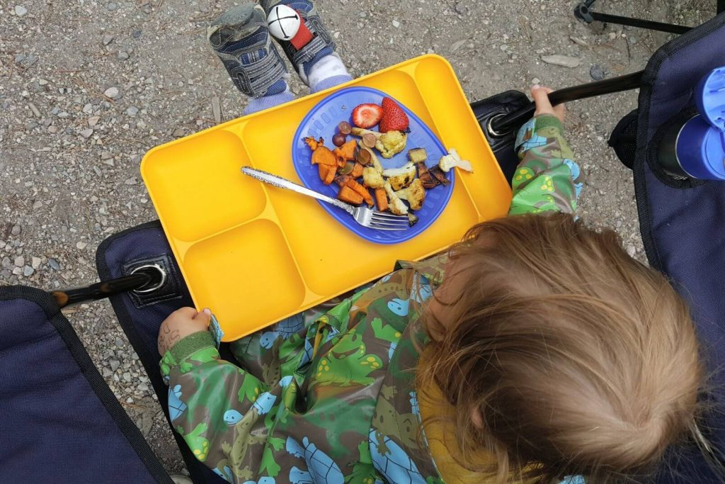 a toddler eating off a yellow tray at the campground
