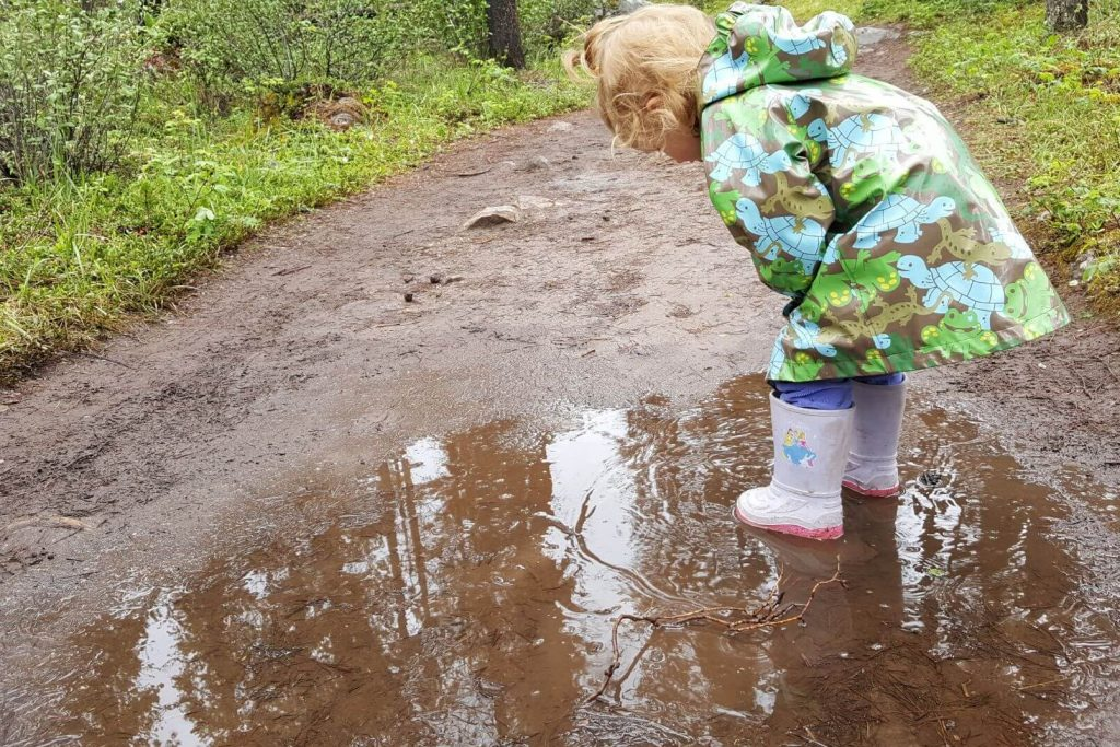 a 2 year old wearing a rain jacket standing in a puddle