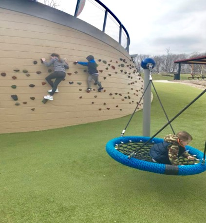 kids playing on a climbing wall at a playground