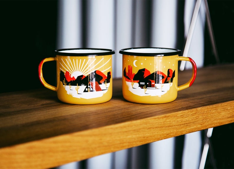 2 yellow enamel mugs with a camping scene printed on them