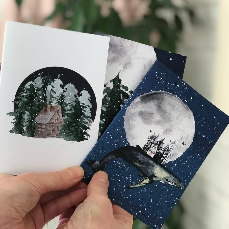 3 different watercolored notebook covers, one with a whale, full moon and forest scene