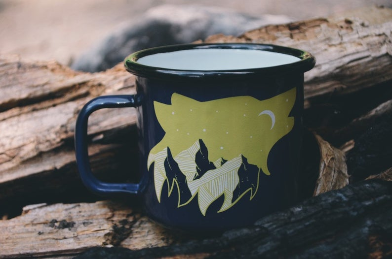 An enamel mug in dark blue with a wolf mountain image, perfect for the outdoorsy dad