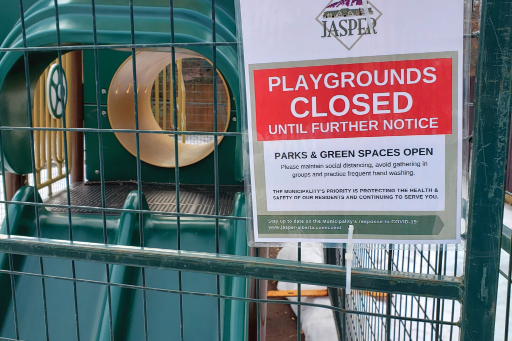 a closed sign on a fenced playground