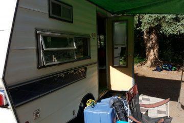 A vintage travel trailer set up at the campsite