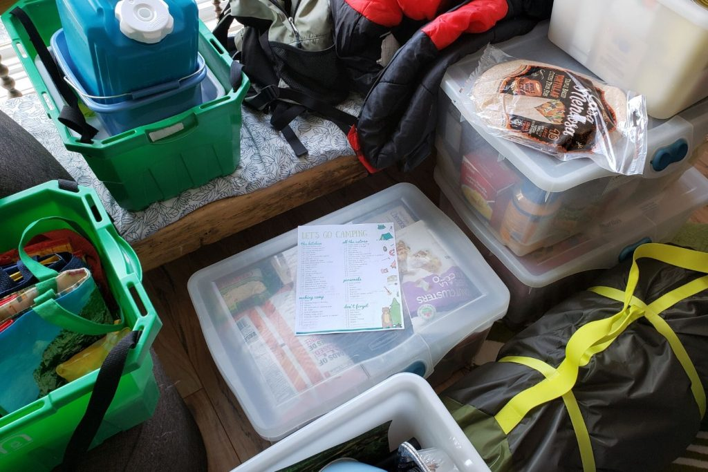 a pile of camping gear and packed tubs