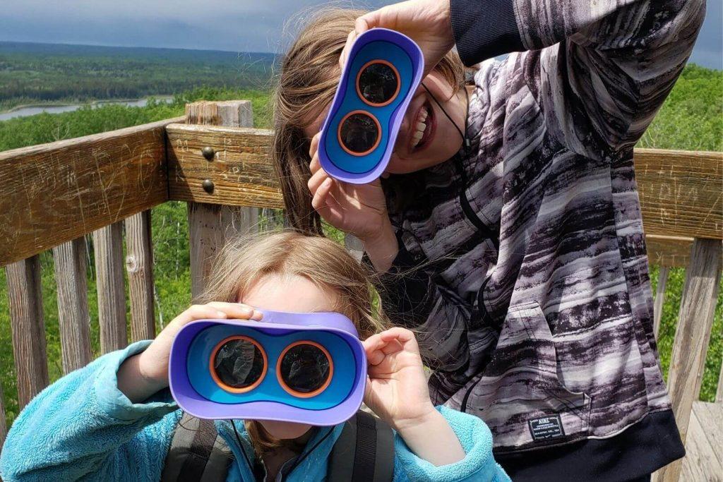 2 kids looking at the camera through kids binoculars