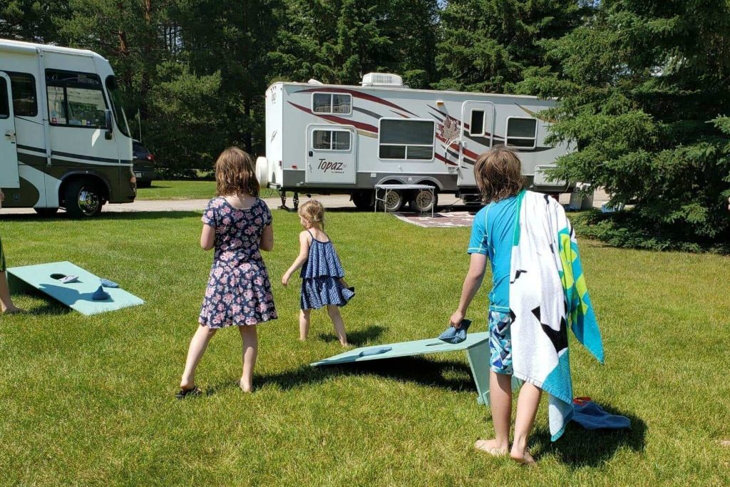 kids playing cornhole or bean bag toss outside at the campsite
