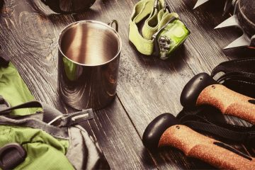 a close up of camping gear, a mug, hiking poles, clamps, and backpack