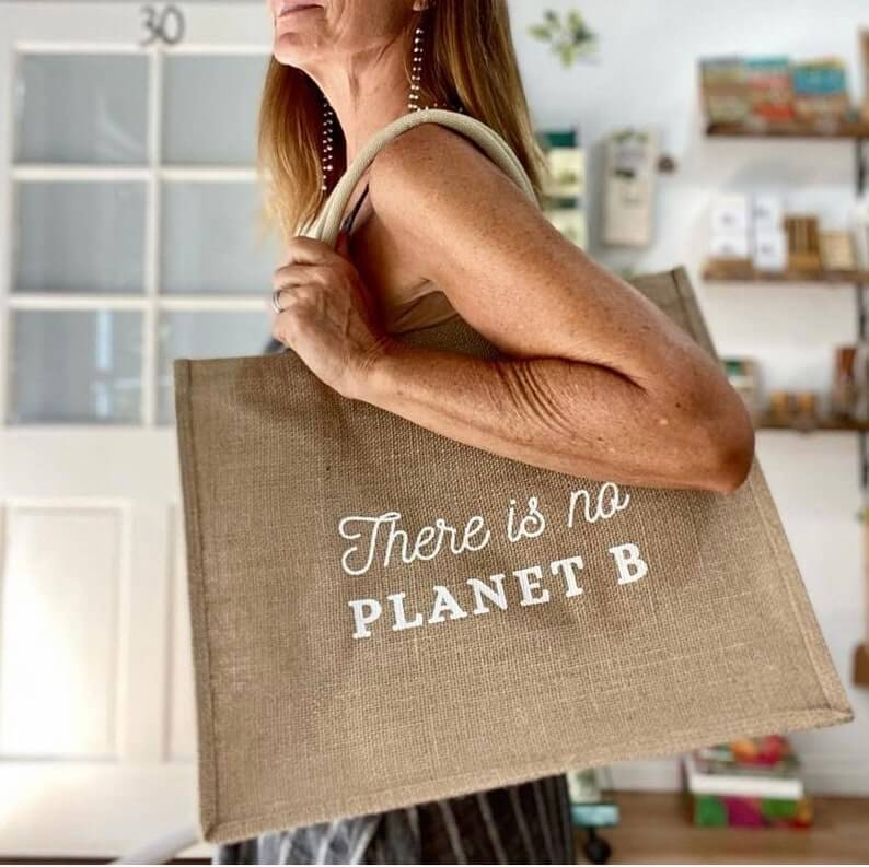 a woman holding an eco friendly reusable jute tote bag